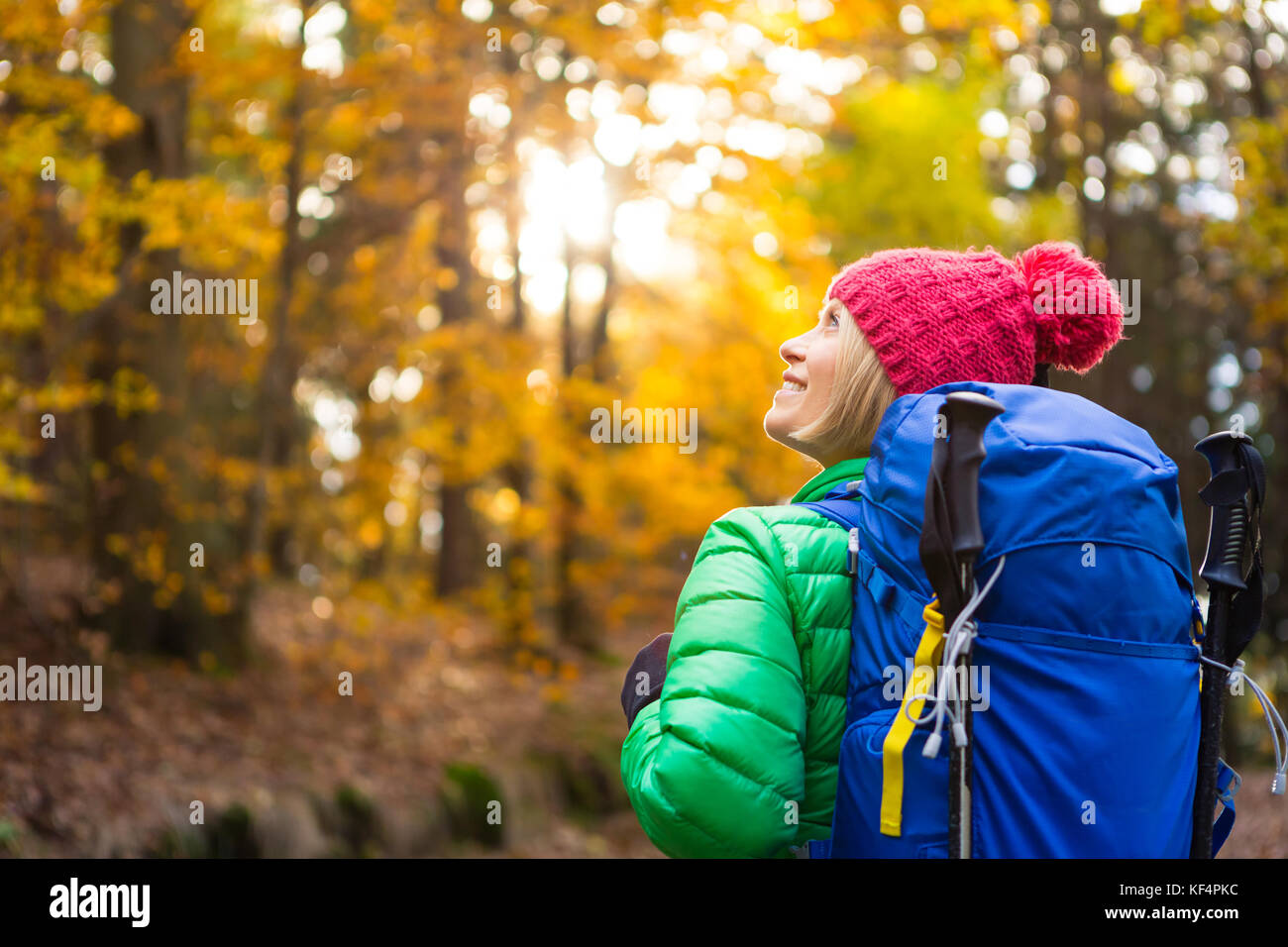 Hiking woman with backpack looking at inspirational autumn golden forest. Fitness travel and healthy lifestyle outdoors - Stock Image