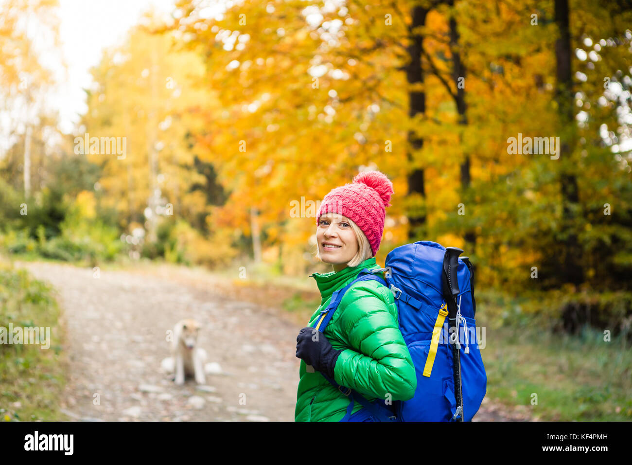 Hiking woman with backpack looking at camera and inspirational autumn golden woods. Fitness travel and healthy lifestyle - Stock Image