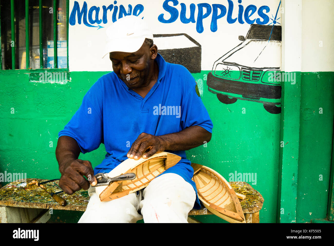 A handcrafter reproduces a traditionnal boat used in the past to catch whales, Bequia, Saint-Vincent and the Grenadines, - Stock Image