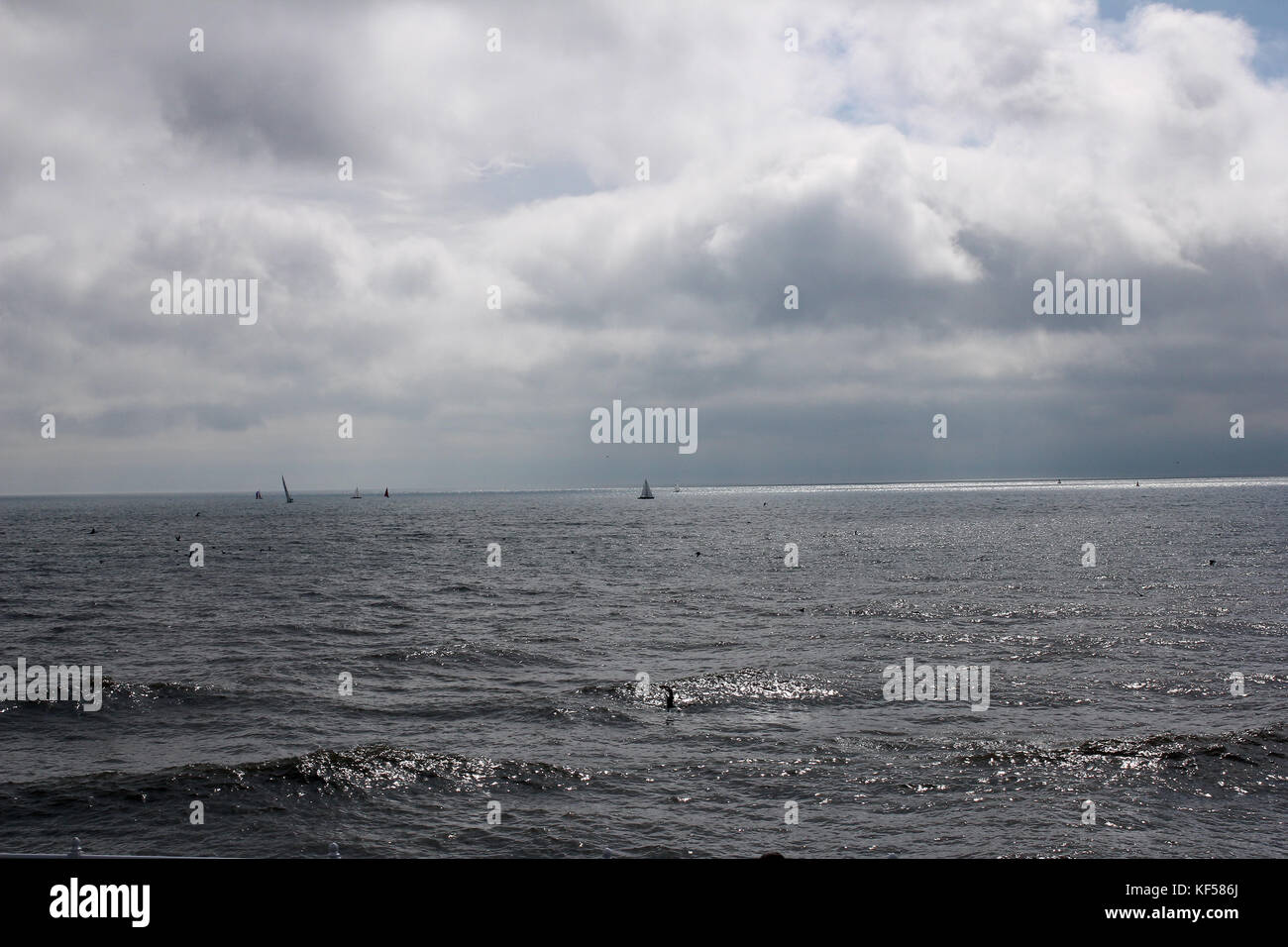 Dramatic sky over the coast with sailing boats and birds - Stock Image