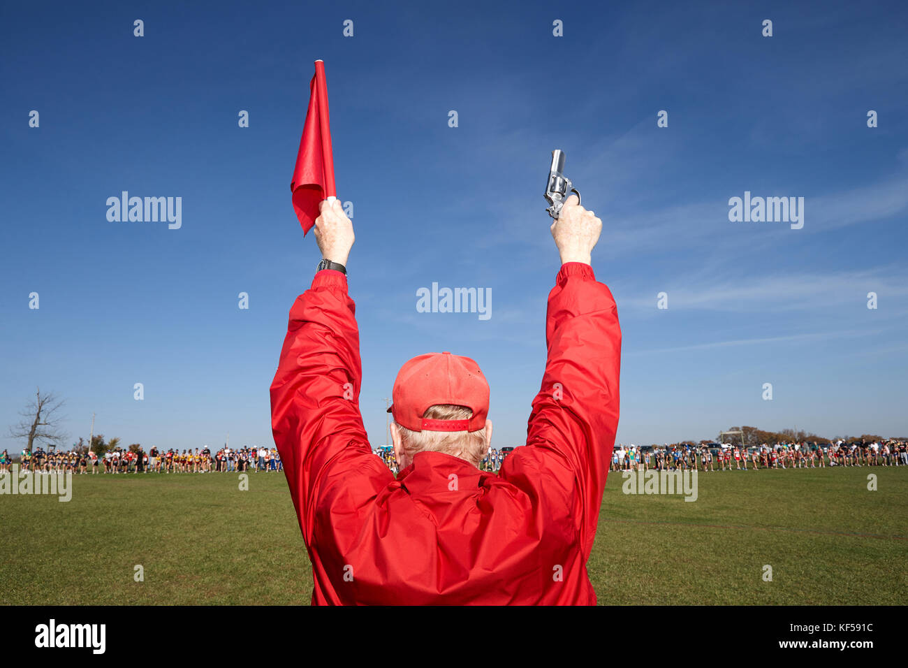 Man dressed all in red standing with his back to the camera facing a field of competitors holding up a starter gun - Stock Image