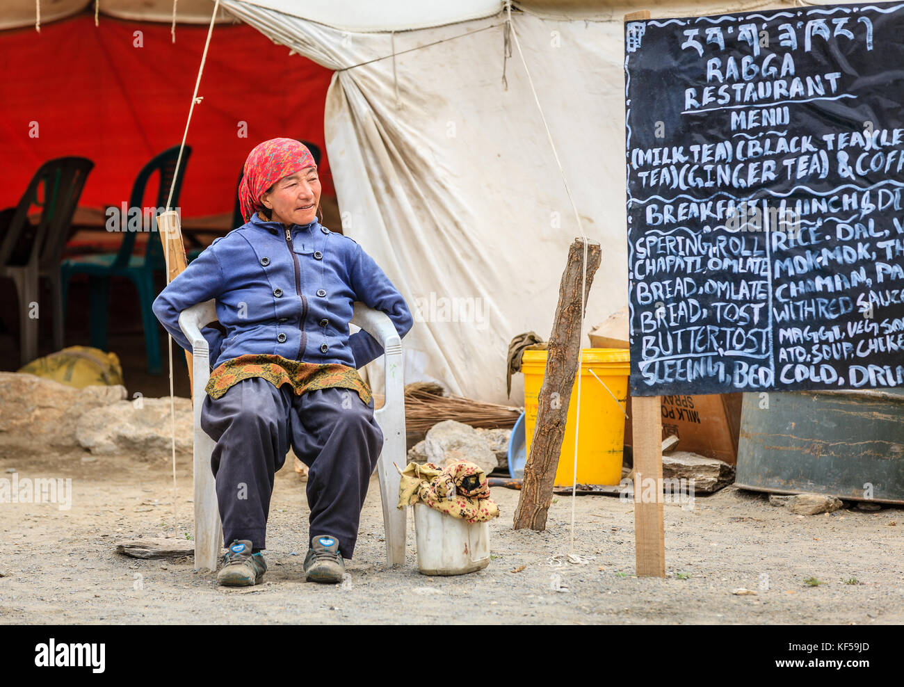 Ladakh, India, July 16, 2016: local woman sits by the menu sign of a roadside canteen in Changthang plateau Ladakh, - Stock Image