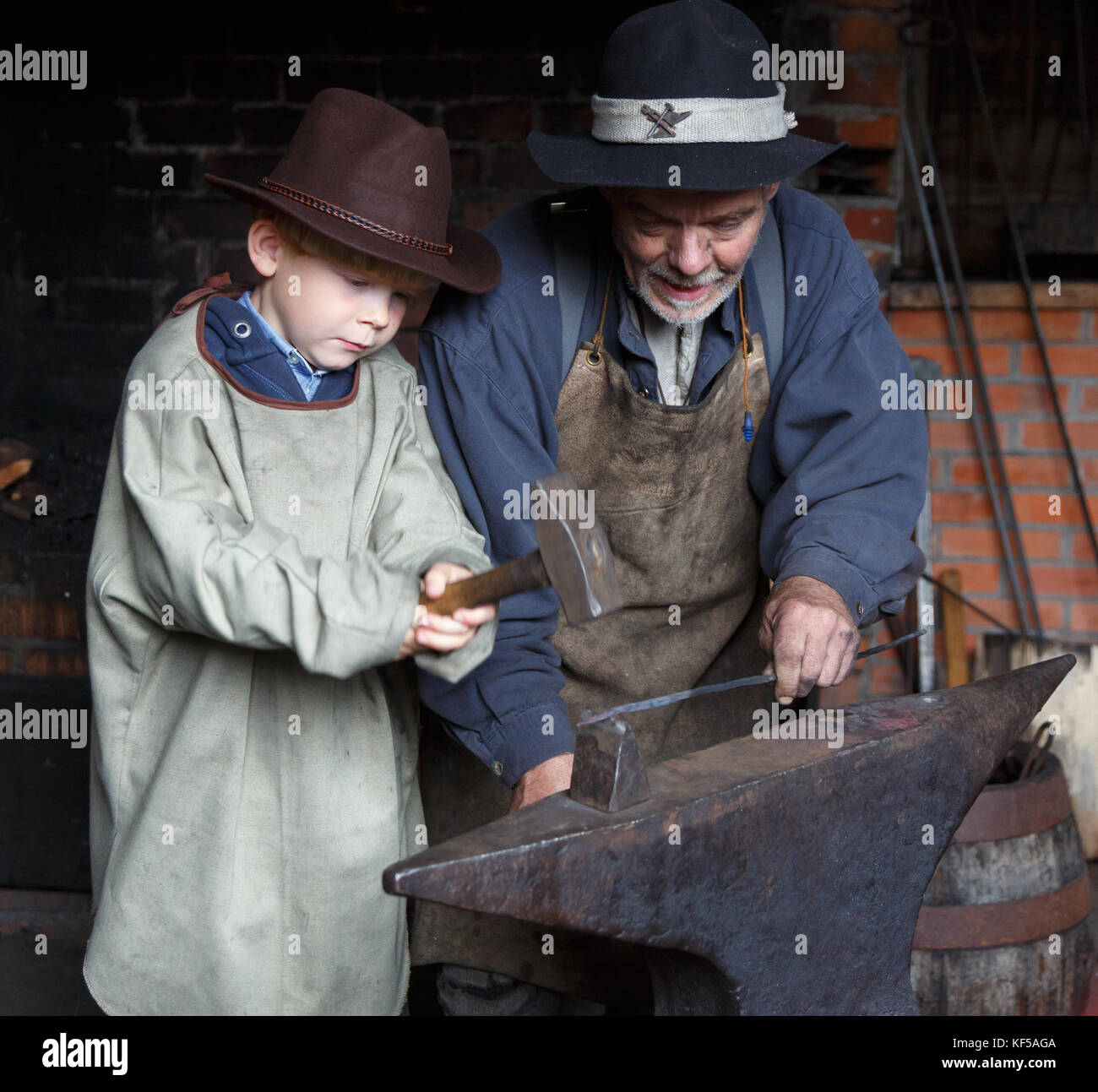 Smith Showing Young Boy How To Do His Handcraft Stock Photo