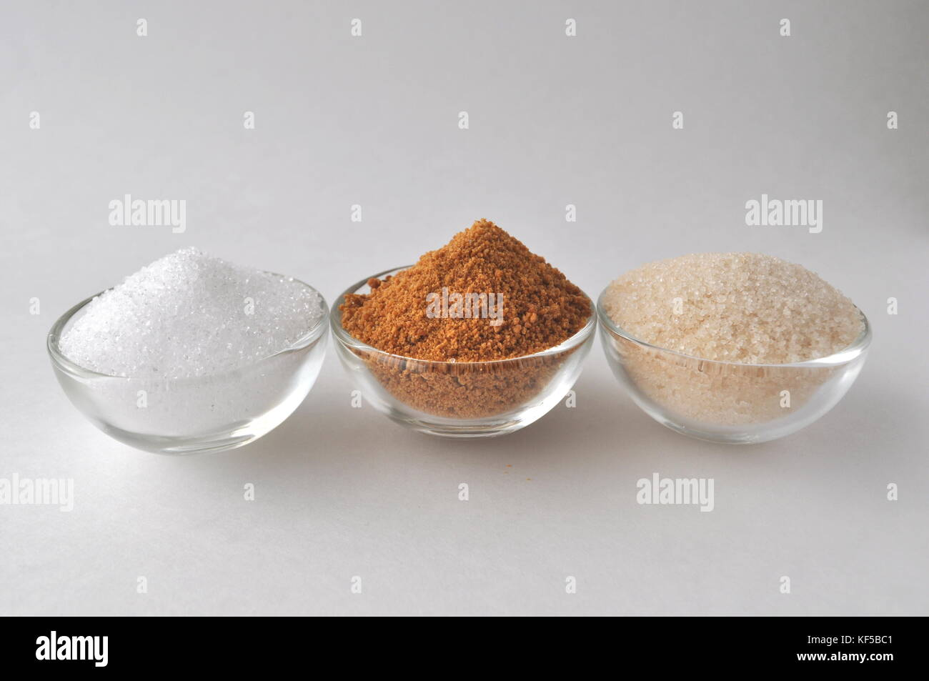 Alternative sweeteners and sugar substitutes - coconut bud sugar, xylitol, cane sugar, maple syrup and honey, isolated - Stock Image