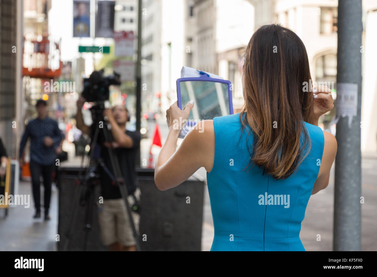 San Francisco, USA -  September 13th, 2017: A female TV reporter is looking her mirror before broadcast at a corner - Stock Image