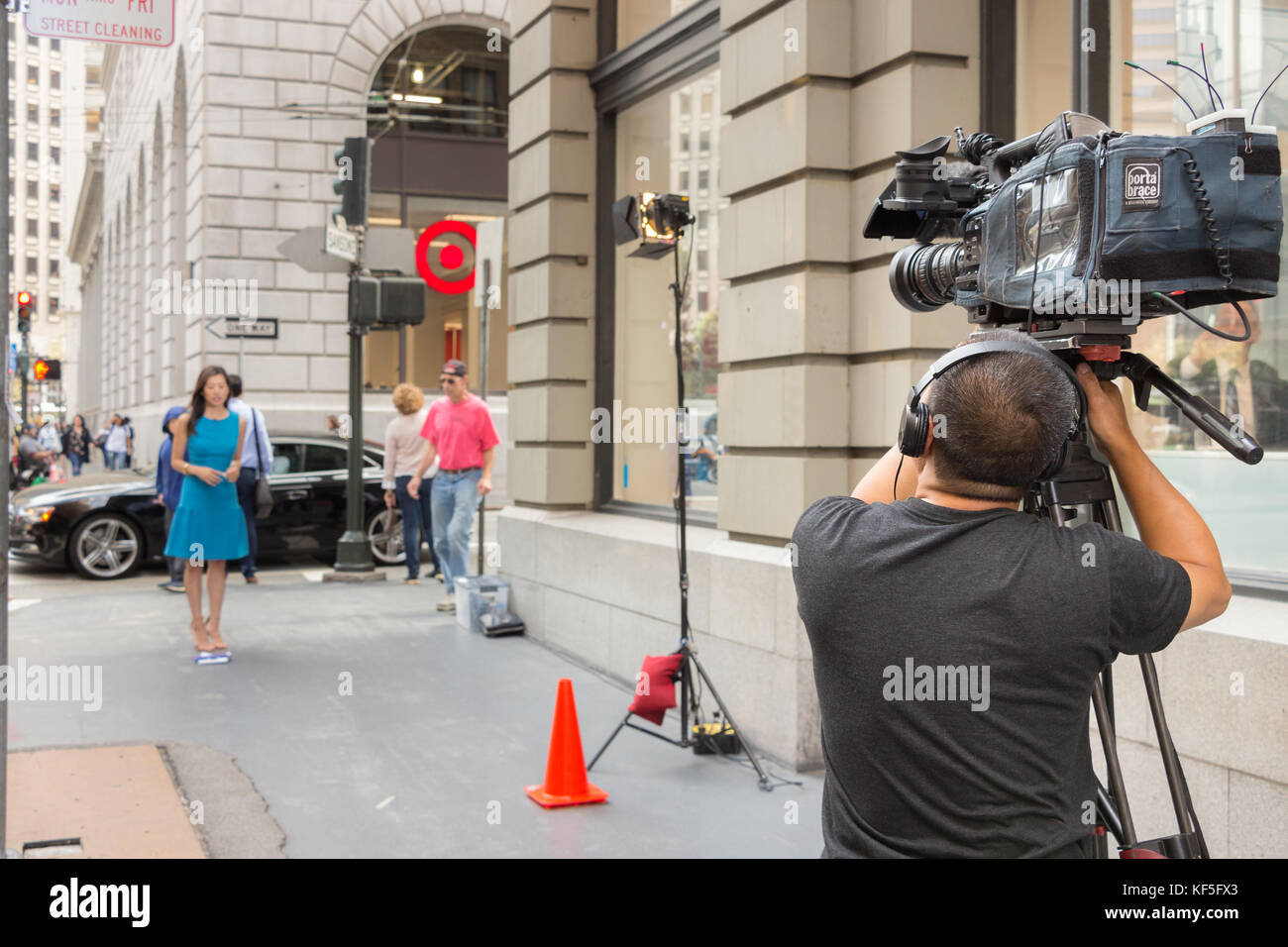 San Francisco, USA -  September 13th, 2017: A male professional cameraman is broadcasting a female journalist at - Stock Image