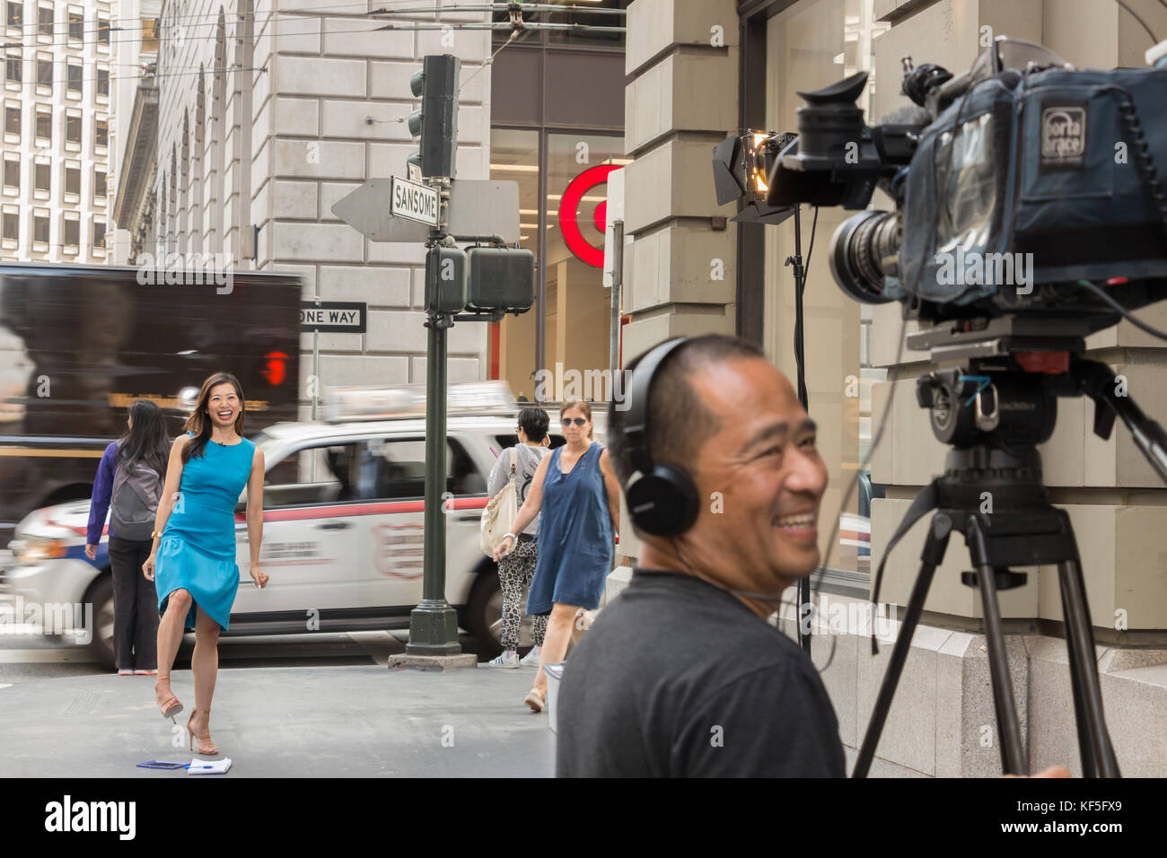 San Francisco, USA -  September 13th, 2017: A female asian TV reporter is laughing with the cameraman before broadcast. - Stock Image