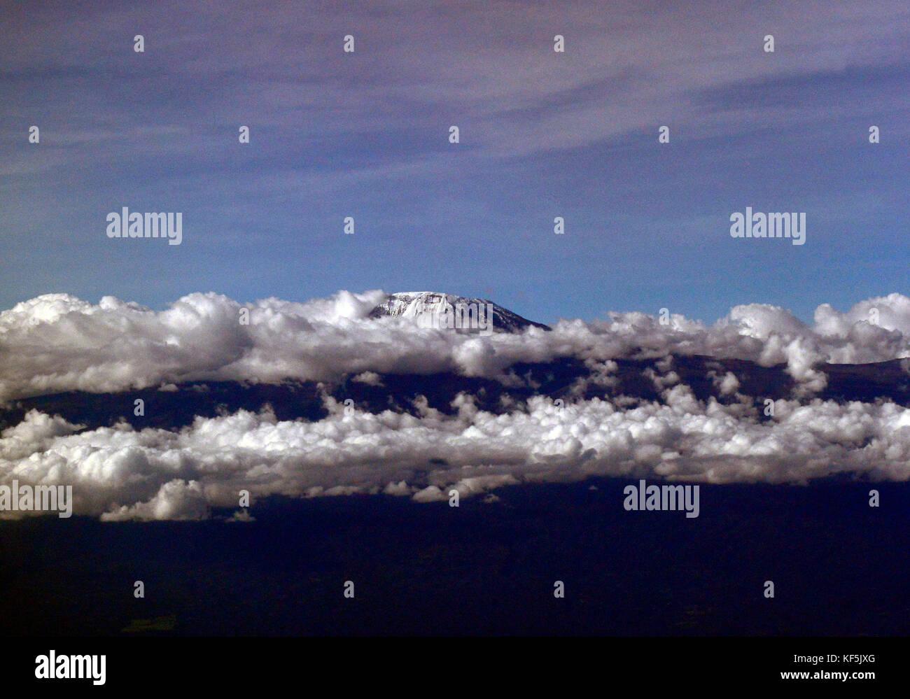 Mount Kilimanjaro peeking above the clouds. - Stock Image