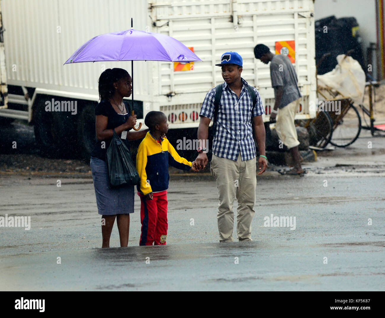 A Tanzanian family walking in the rain. - Stock Image