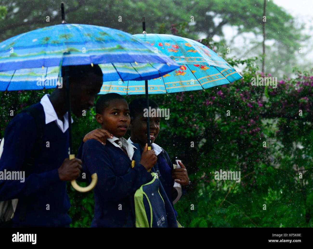 Tanzanian children walking in the heavy rain. - Stock Image