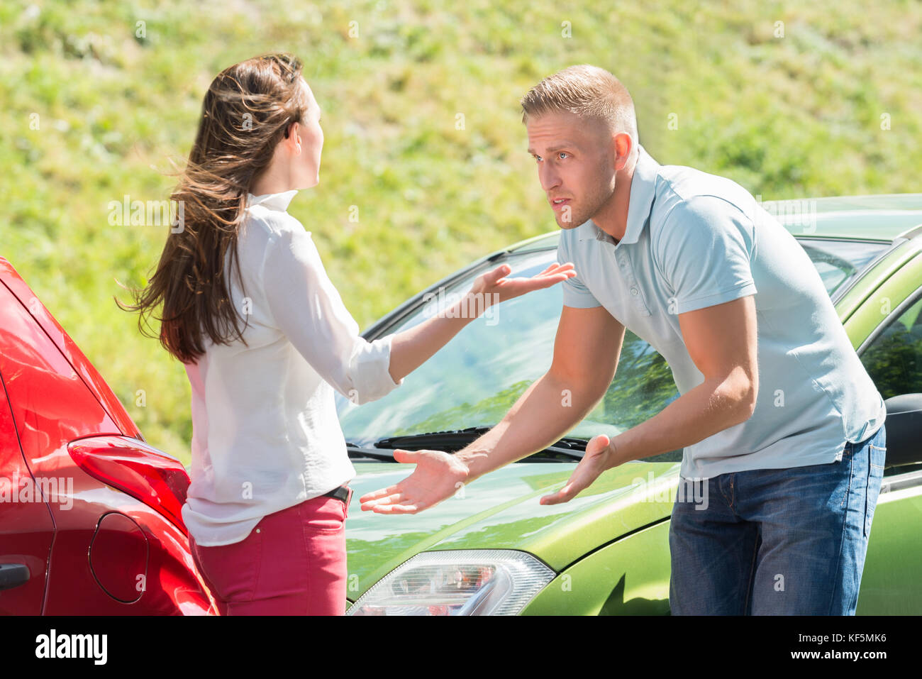 Unhappy Young Couple Arguing With Each Other On Street - Stock Image