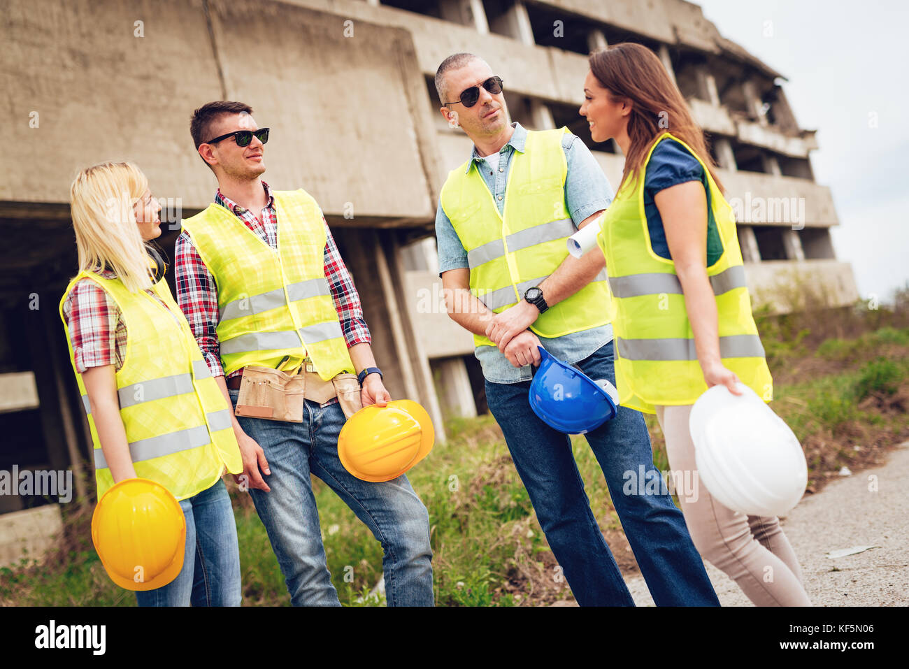 Four construction architects talking in front building damaged in the disaster. - Stock Image