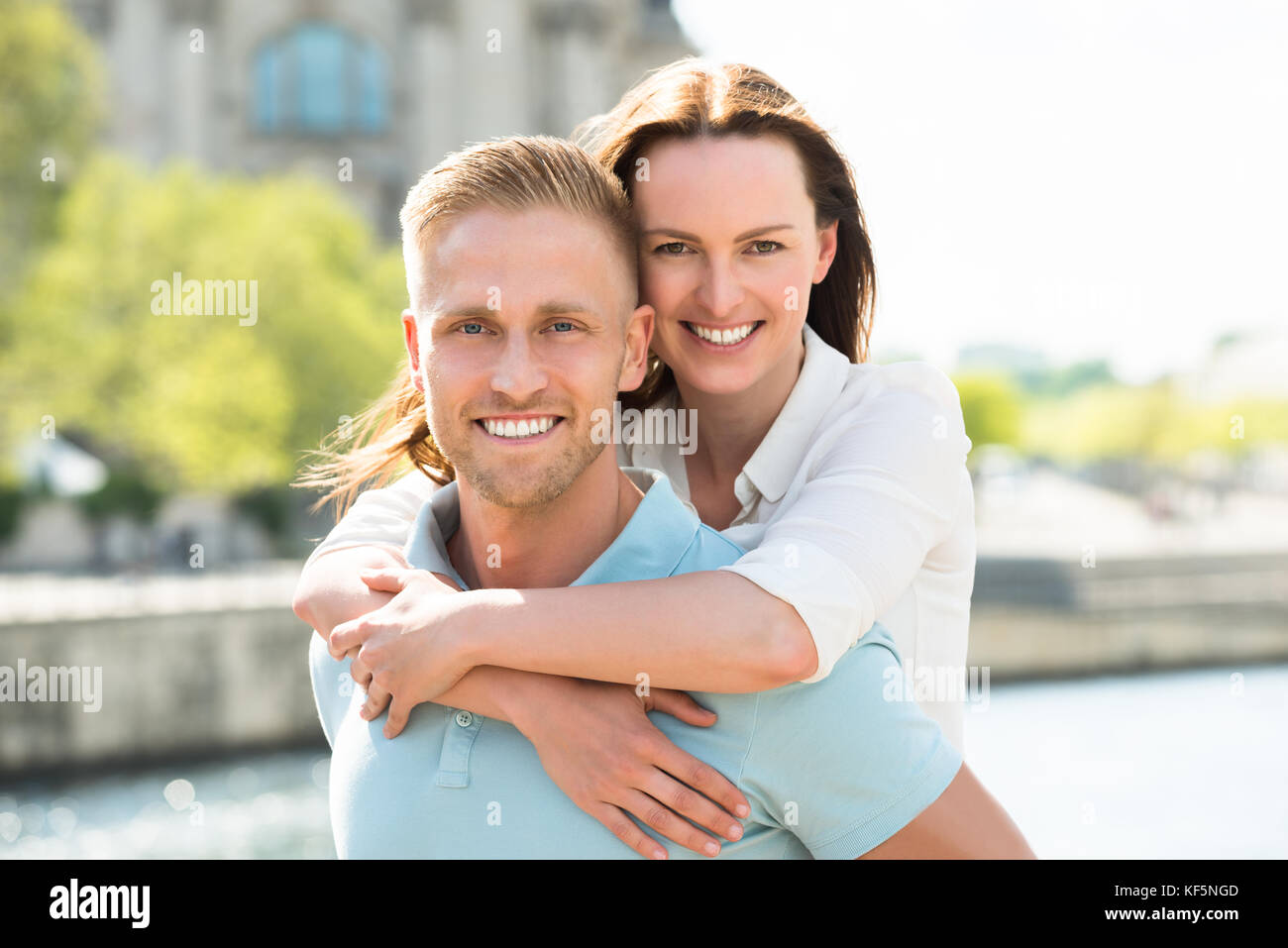 Portrait Of Young Happy Man Carrying Woman On His Back - Stock Image