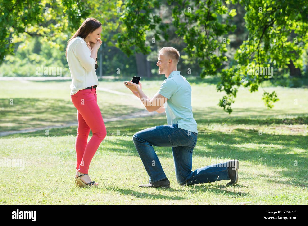 Man Kneeling And Making Proposal To Woman At Park - Stock Image