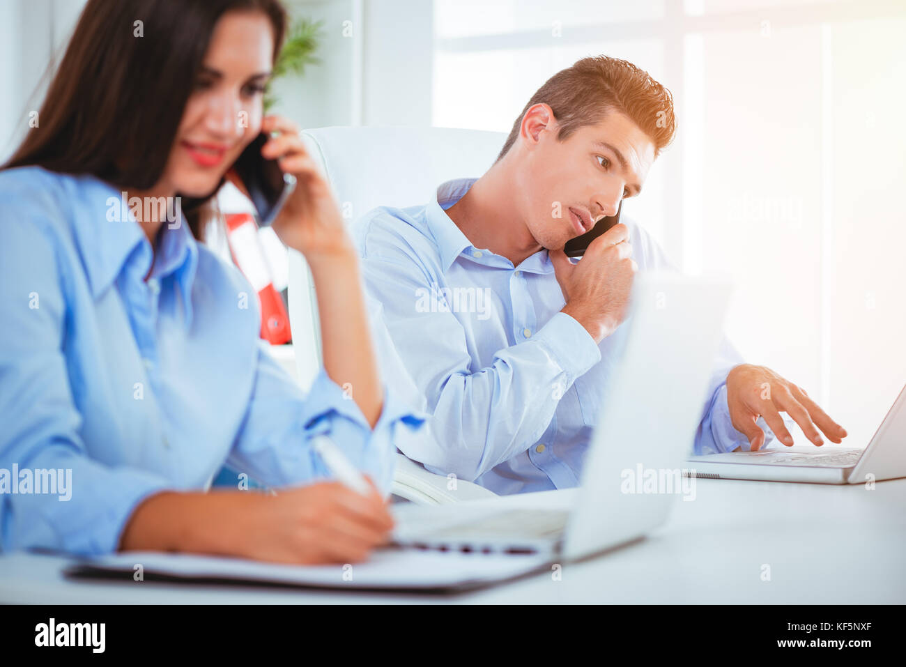 Two businesspeople sitting at the office table. Woman is writing and man using smartphone and looking at laptop. - Stock Image
