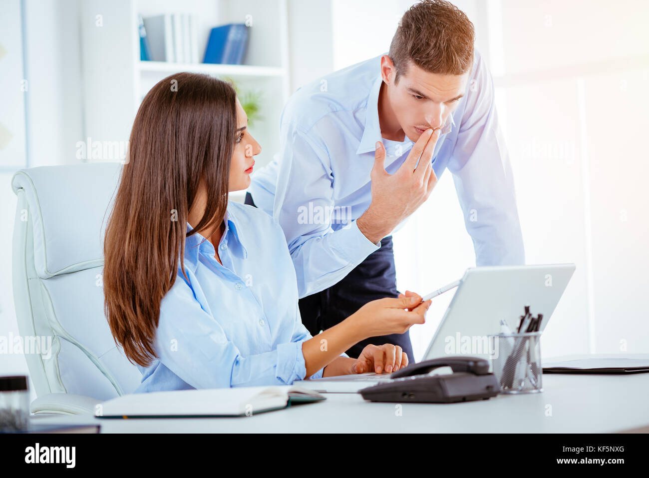 Two young business people talking in the office. Woman sitting at an office desk, behind her standing a young man - Stock Image