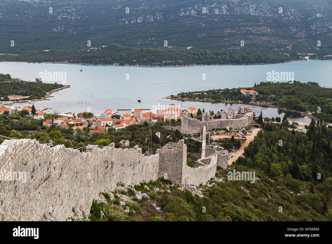 Looking down one side of the long walls of Ston (Croatia) towards Mali Ston, a town rich in oyster and mussel farming. - Stock Image