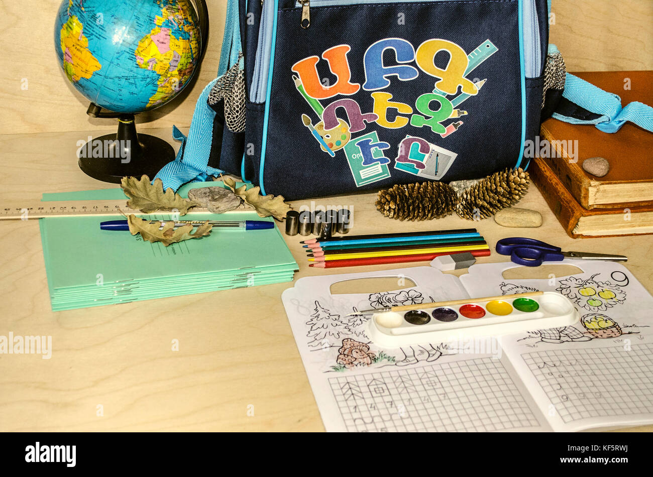 First school supplies exercise book,pencils,paints,scissors and blue backpack with letters - Stock Image