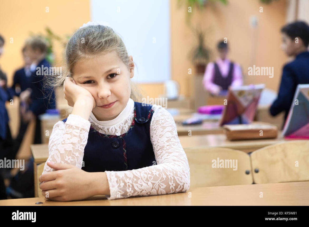 Young girl a pupil is in a bad temper on recess while other children playing on background - Stock Image