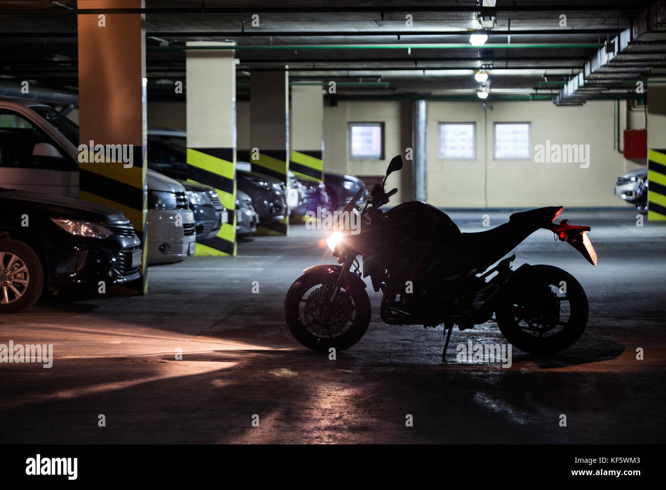 Silhouette of motorcycle standing with running engine in front of parked vehicles in underground parking - Stock Image