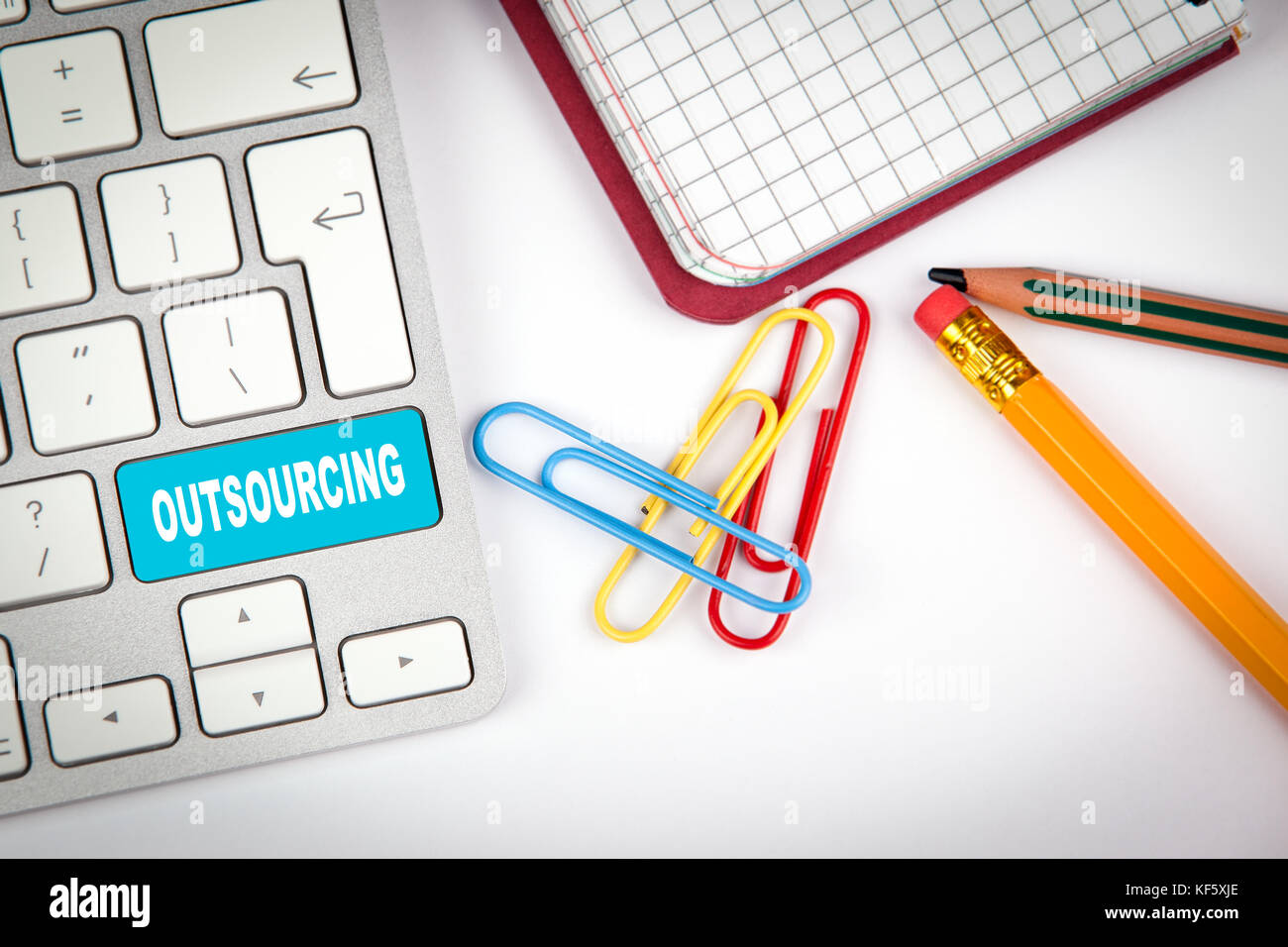 Outsourcing concept. Computer keyboard on a white office desk with various items - Stock Image