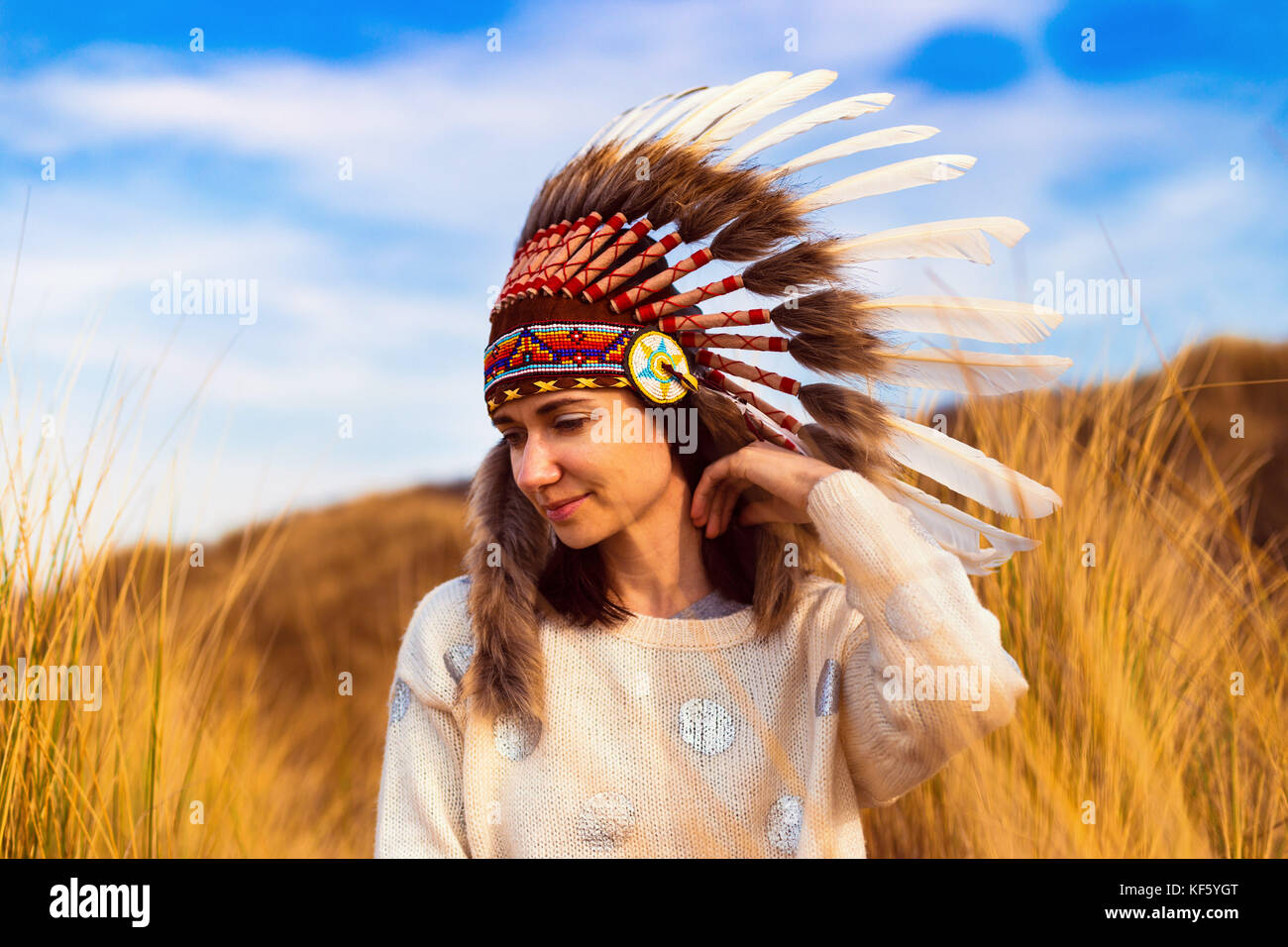 Beautiful young woman in black dotted white chief style Native American headdress during sunset - Stock Image
