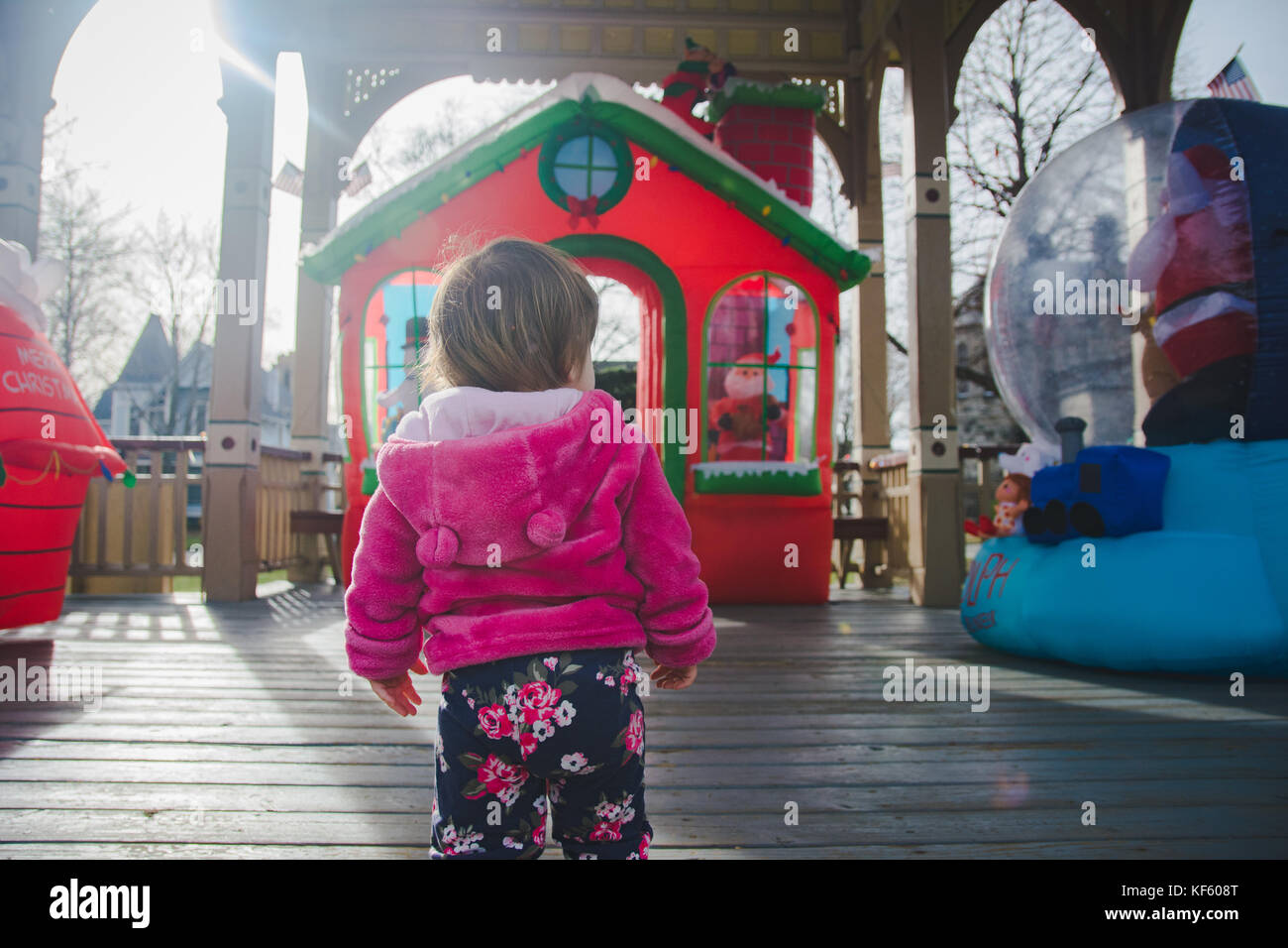 Toddler walking toward Christmas or holiday displays. Stock Photo