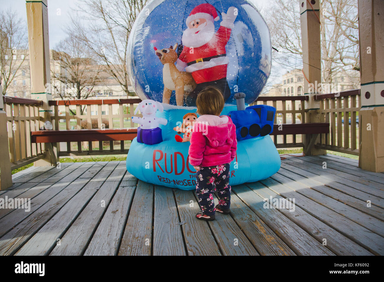 Toddler walking toward Christmas or holiday displays. - Stock Image