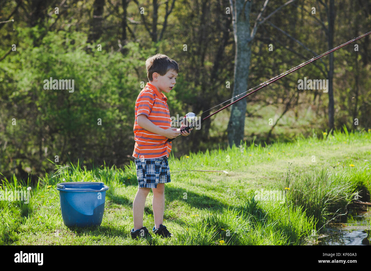 5-6 year old boy fishing by a pond in summer. - Stock Image