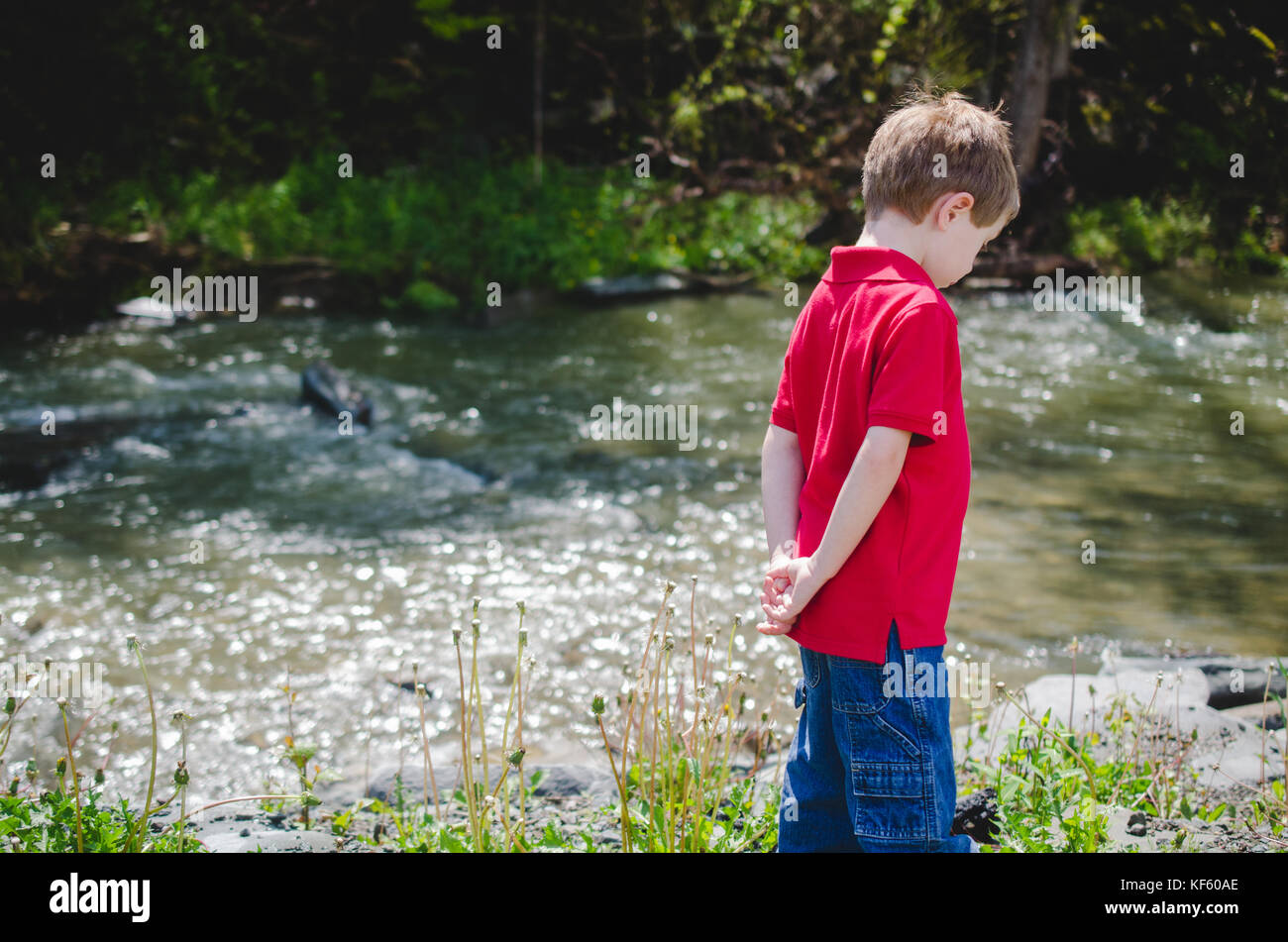 A young boy stands by a stream with his hands behind his back and his back to the camera. - Stock Image