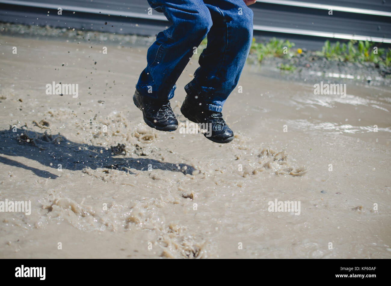 Child jumping in a mud puddle feet only - Stock Image
