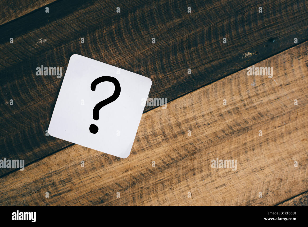 question mark on white note on a wooden background - Stock Image