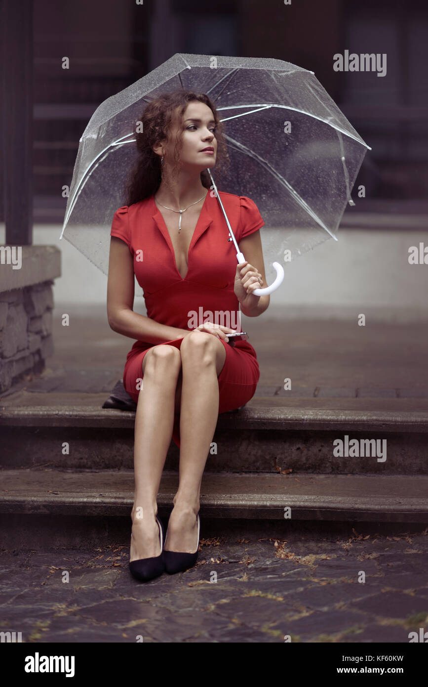 Young woman in a red elegant dress waiting for someone sitting on the stairs with an umbrella in the rain on a city Stock Photo