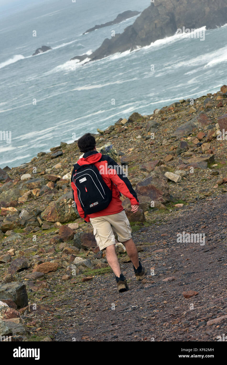 a man walking along the clifftop in Cornwall on the south west coast path wearing outdoor clothing and waterproof - Stock Image