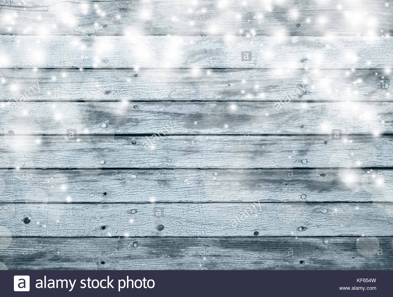 Textured wooden boards with illustrated abstract blurred white snowflakes, copy space background. Winter holiday - Stock Image
