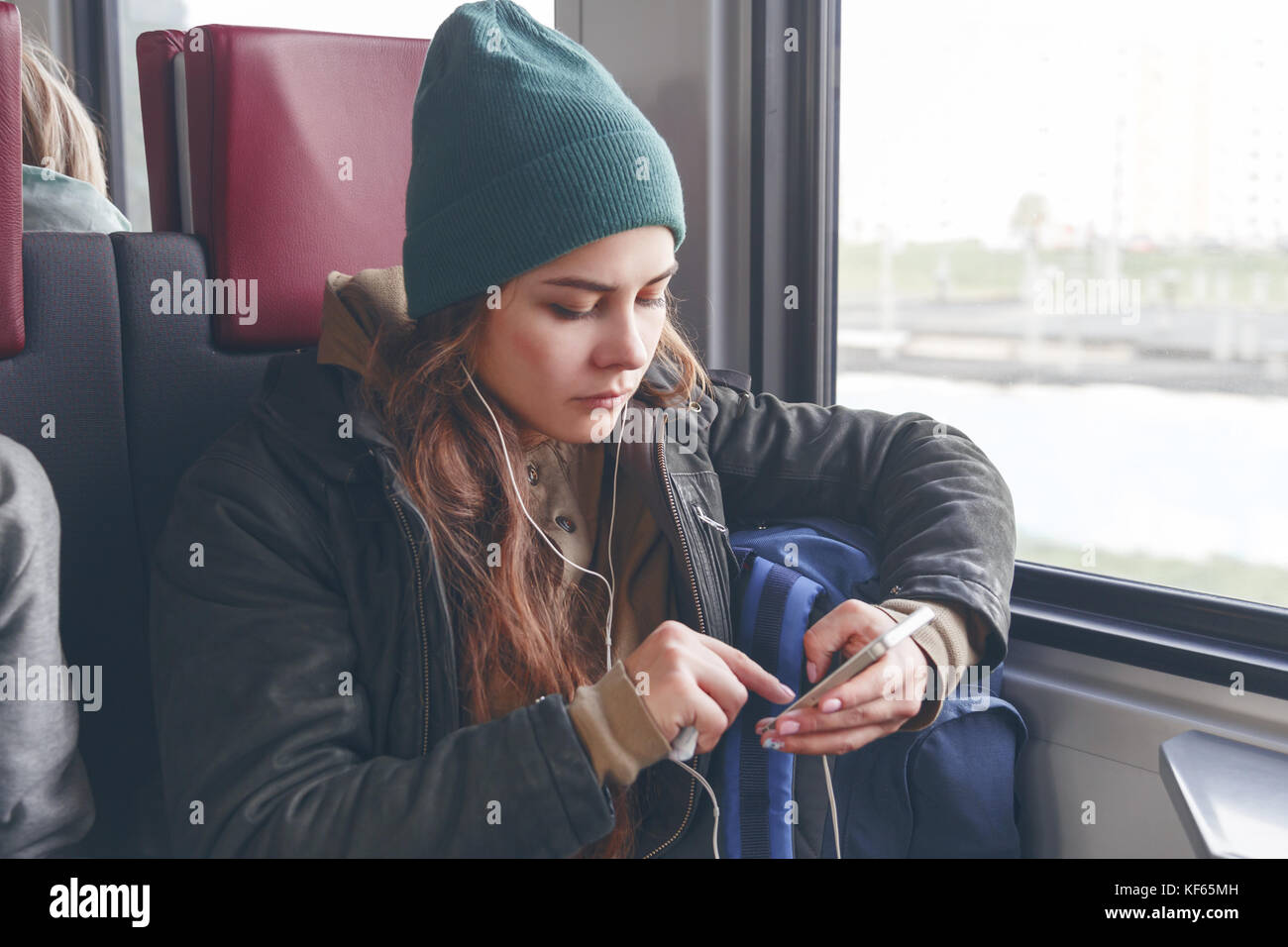 Modern people city lifestyle. Young urban woman using phone app and wireless headphones to listen to music or play Stock Photo