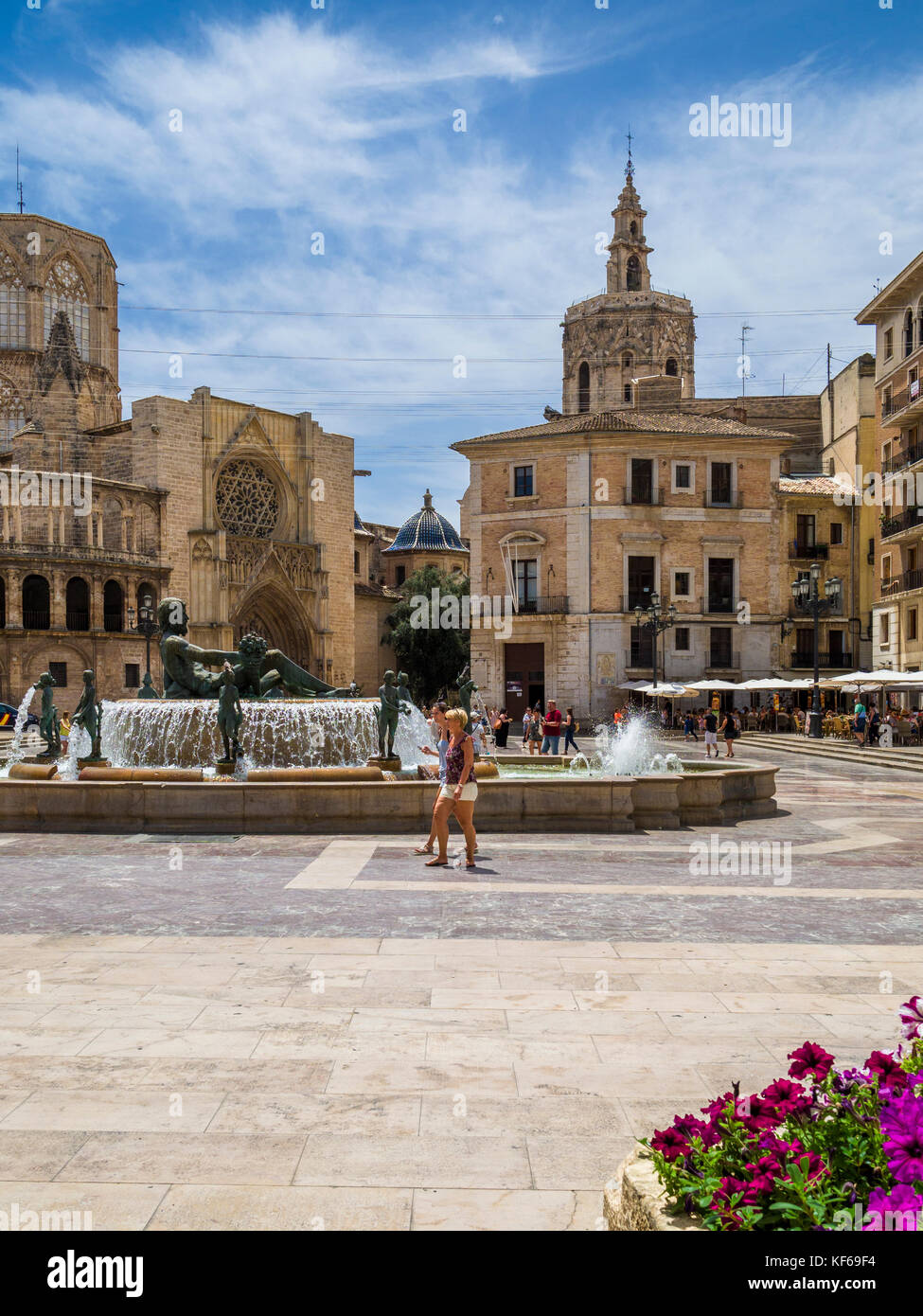 Two people walking by Turia fountain in the old town with the Cathedral (left) and it's tower, el Miguelete (centre) Stock Photo