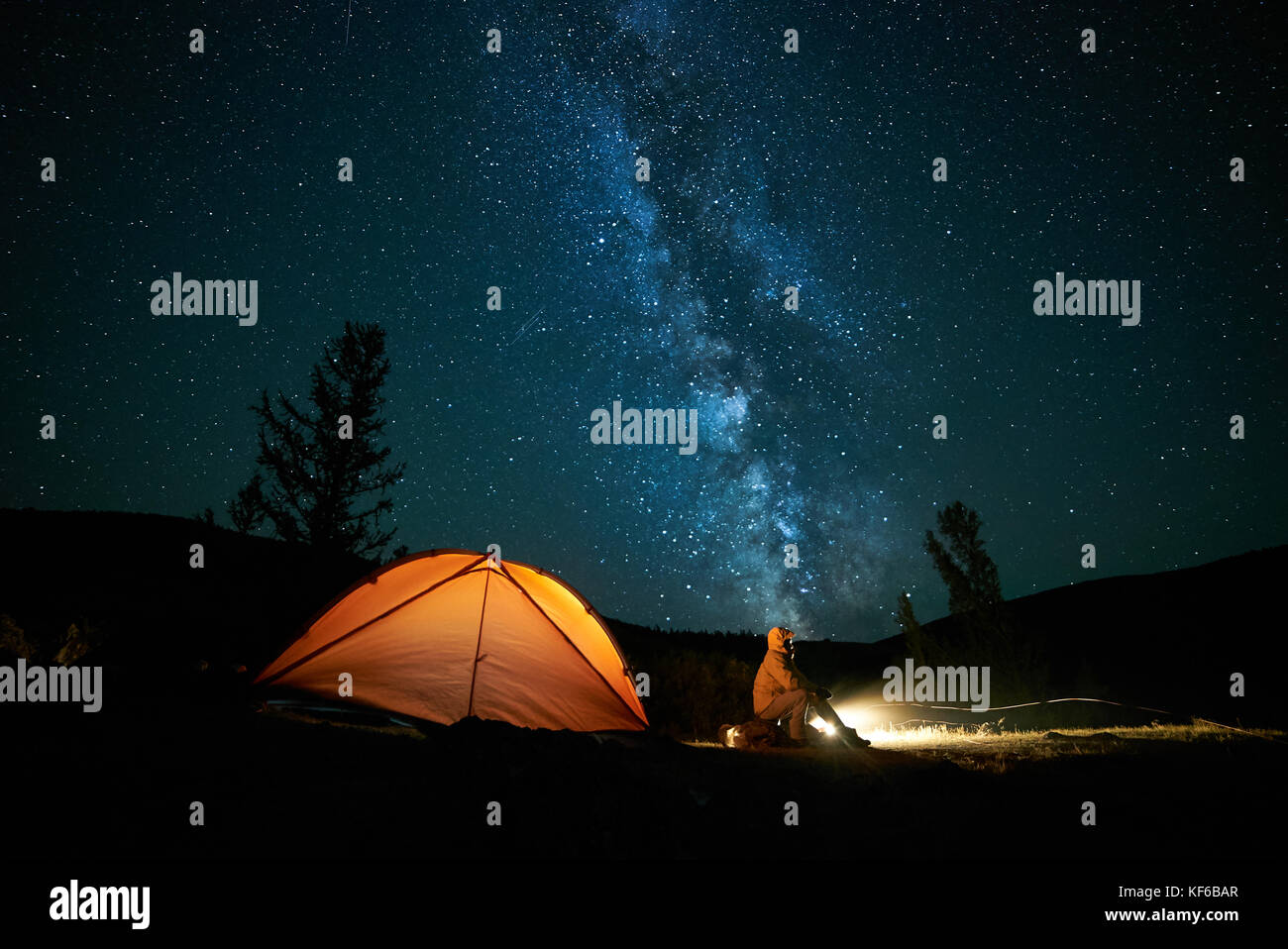 Tourist near his camp tent at night. - Stock Image