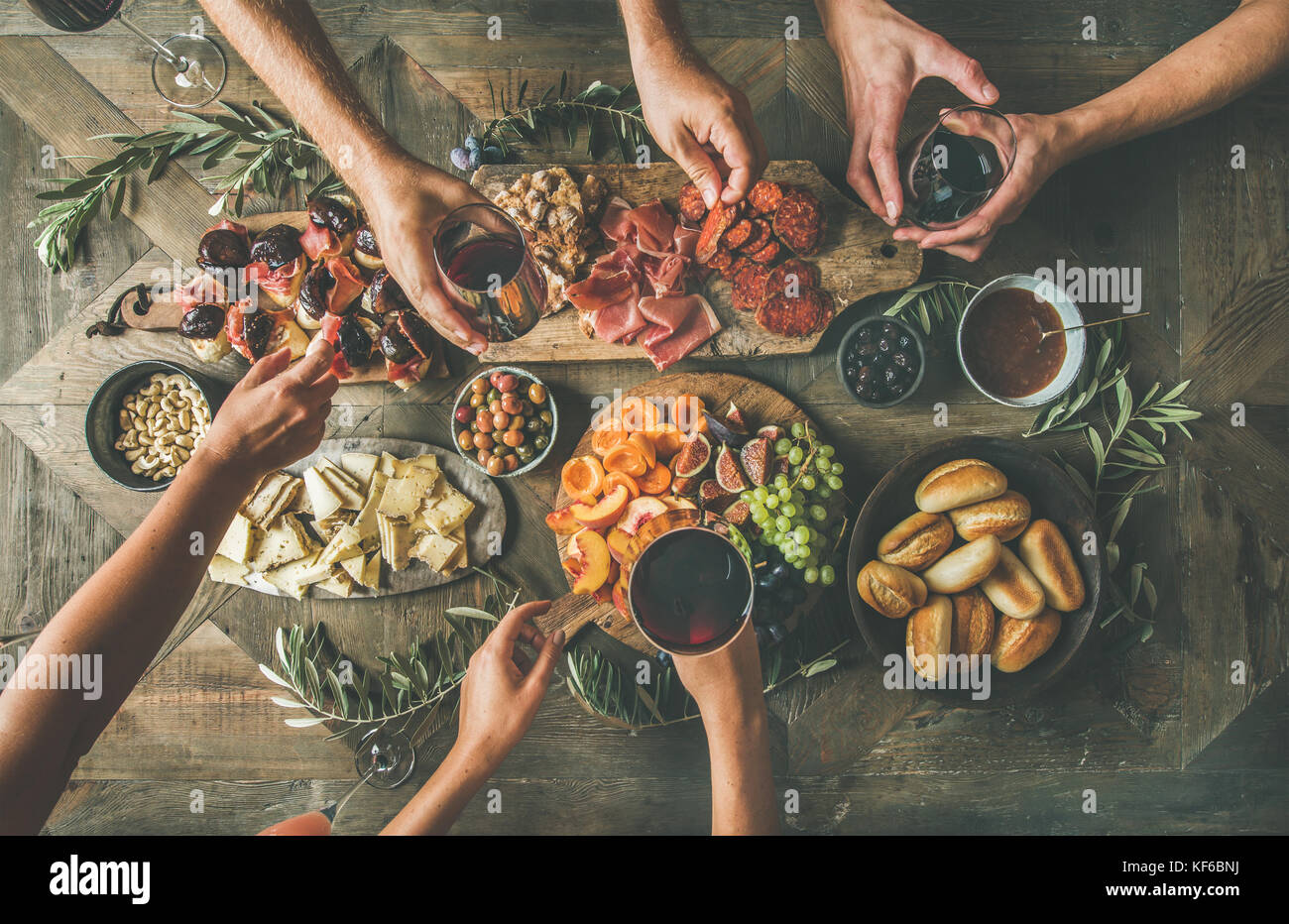 Top view of people drinking and eating together over table - Stock Image