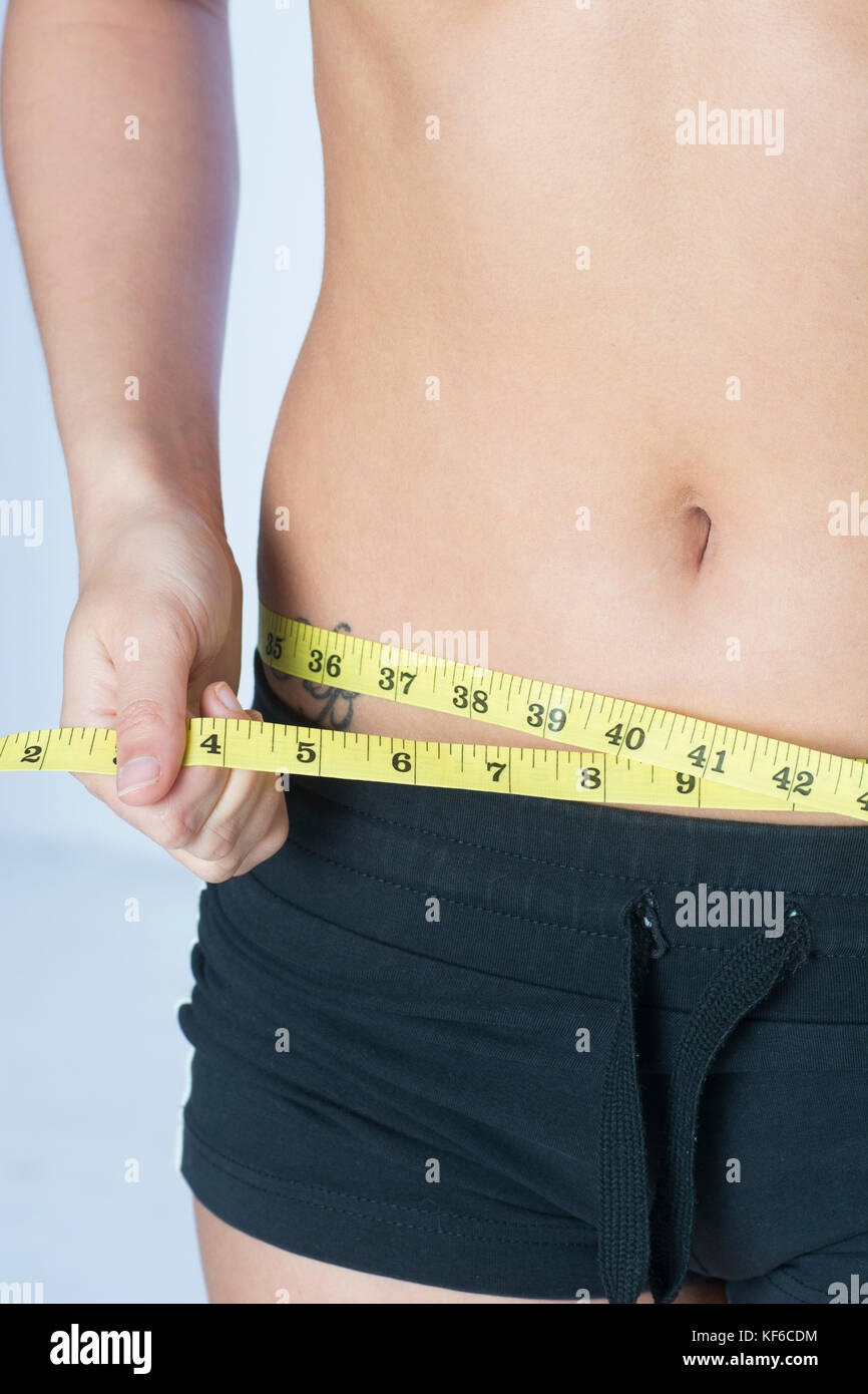 Close up of a young woman measuring her waist with a tape measure - Stock Image