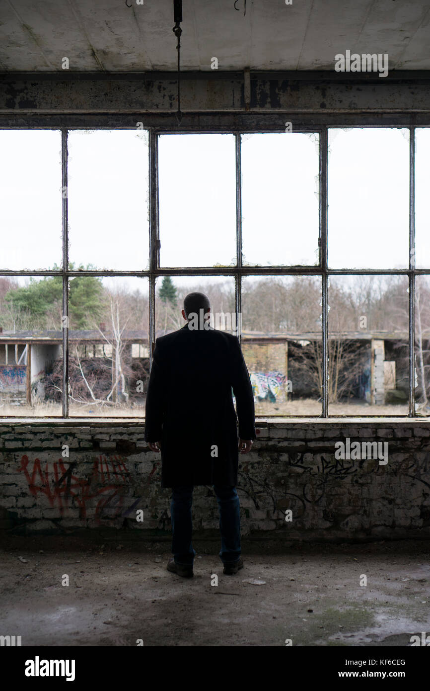 Rear view of a man wearing a coat standing by broken windows insisde a derelict building - Stock Image