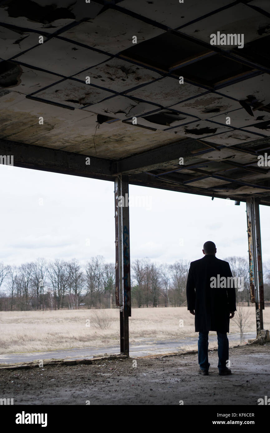 Rear view of a man wearing a coat standing inside a derelict building - Stock Image