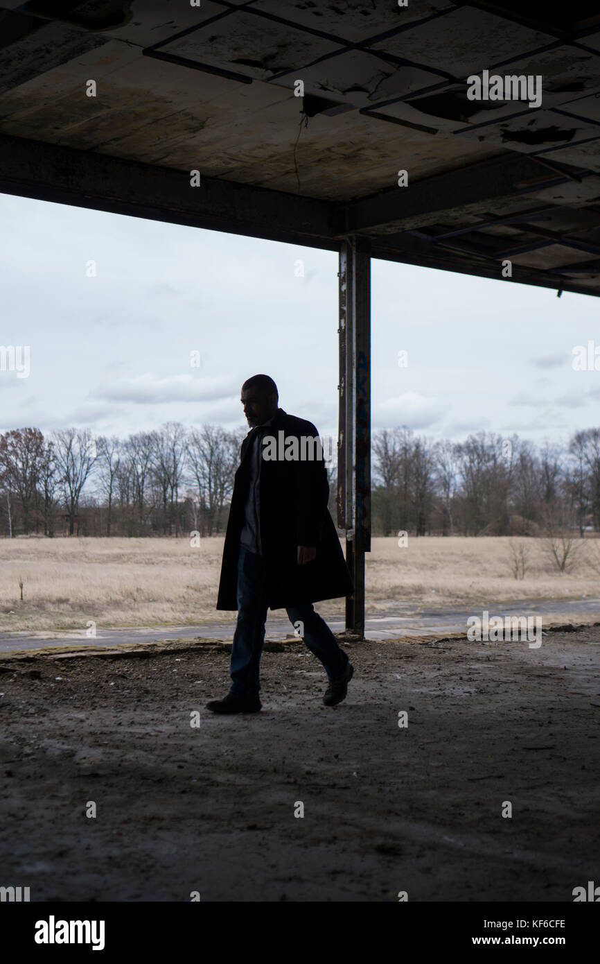 Side view of a man wearing a coat walking inside a derelict building - Stock Image