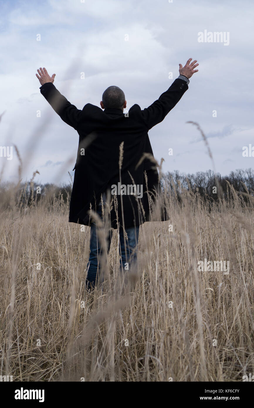 Rear view of a man wearing a coat standing a field arms outstretched - Stock Image