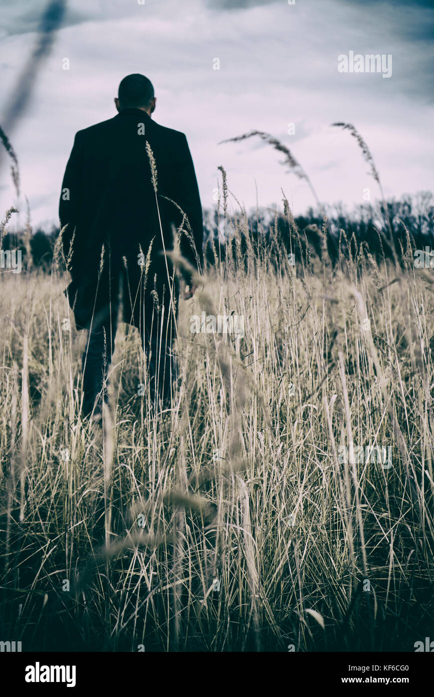 Rear view of a man wearing a coat standing in a field Stock Photo