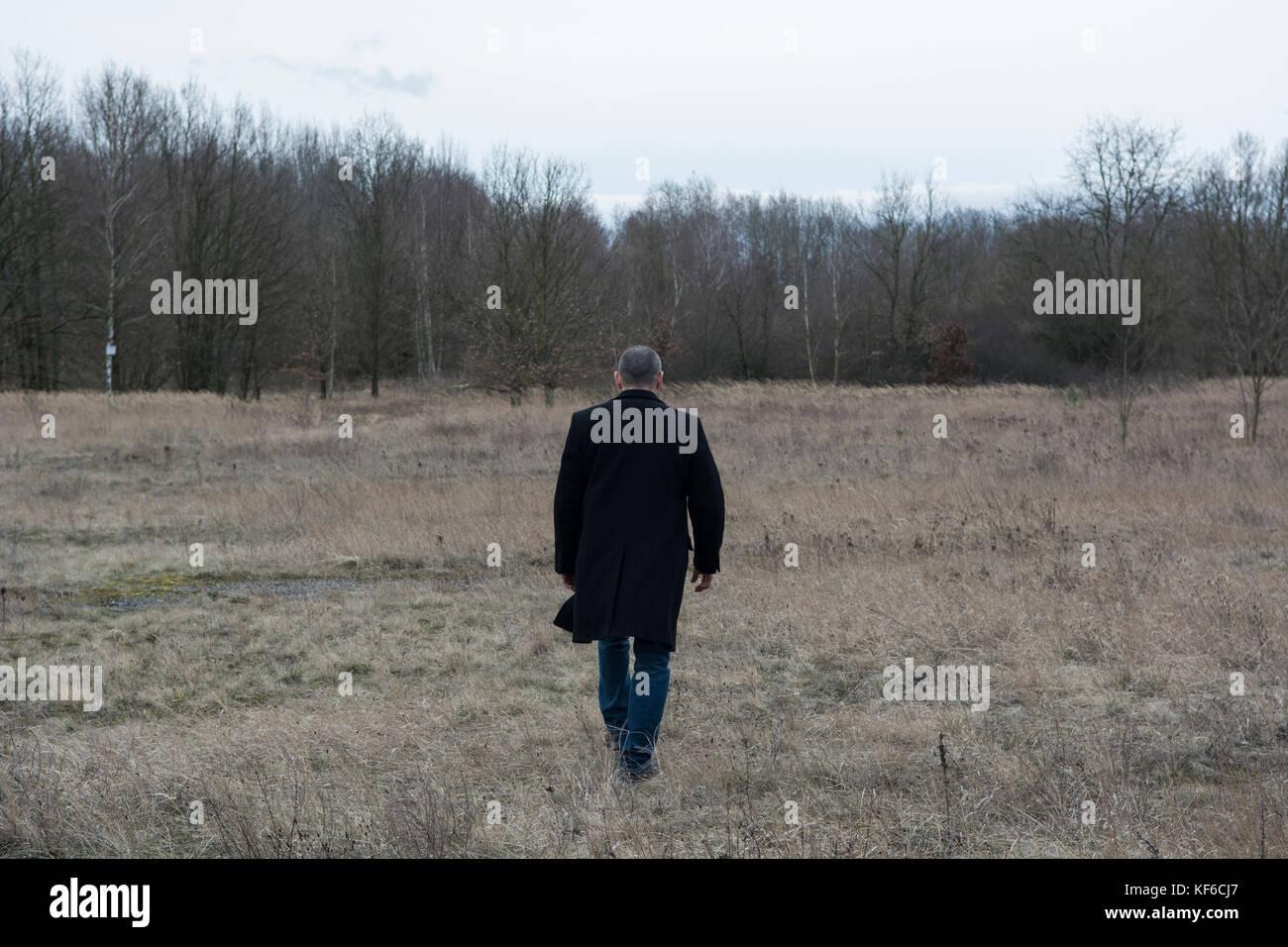 Full length rear view of a man wearing a coat walking away in a field - Stock Image