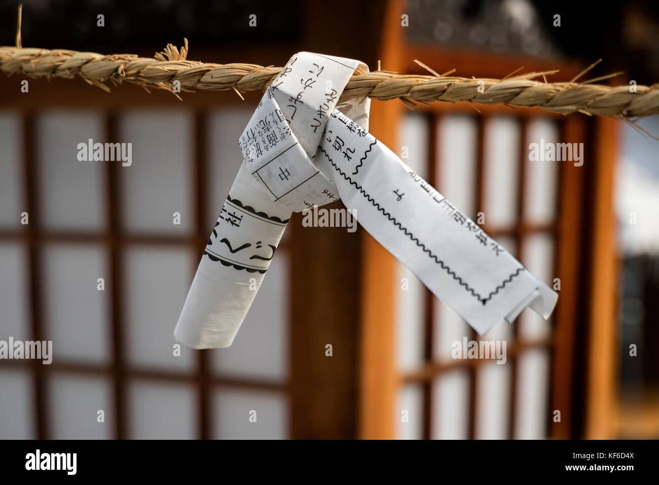 Hiroshima, Japan - May 25, 2017: Close up of a fortune telling paper strip tied up on a rope, omikuji, it is left - Stock Image