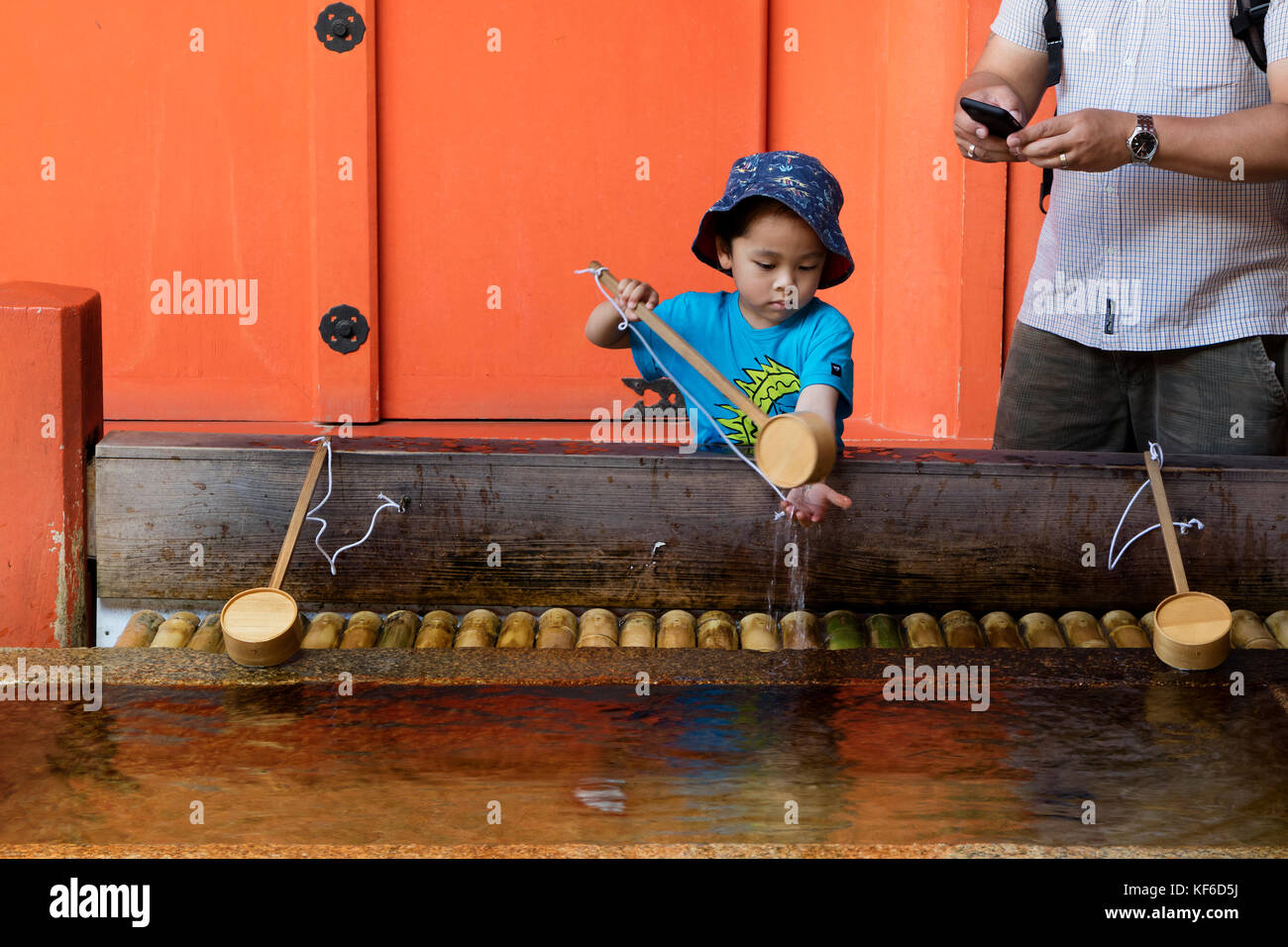 Miyajima - Japan, May 26, 2017: Child is cleaning hands at a purification fountain of the famous the Itsukushima - Stock Image