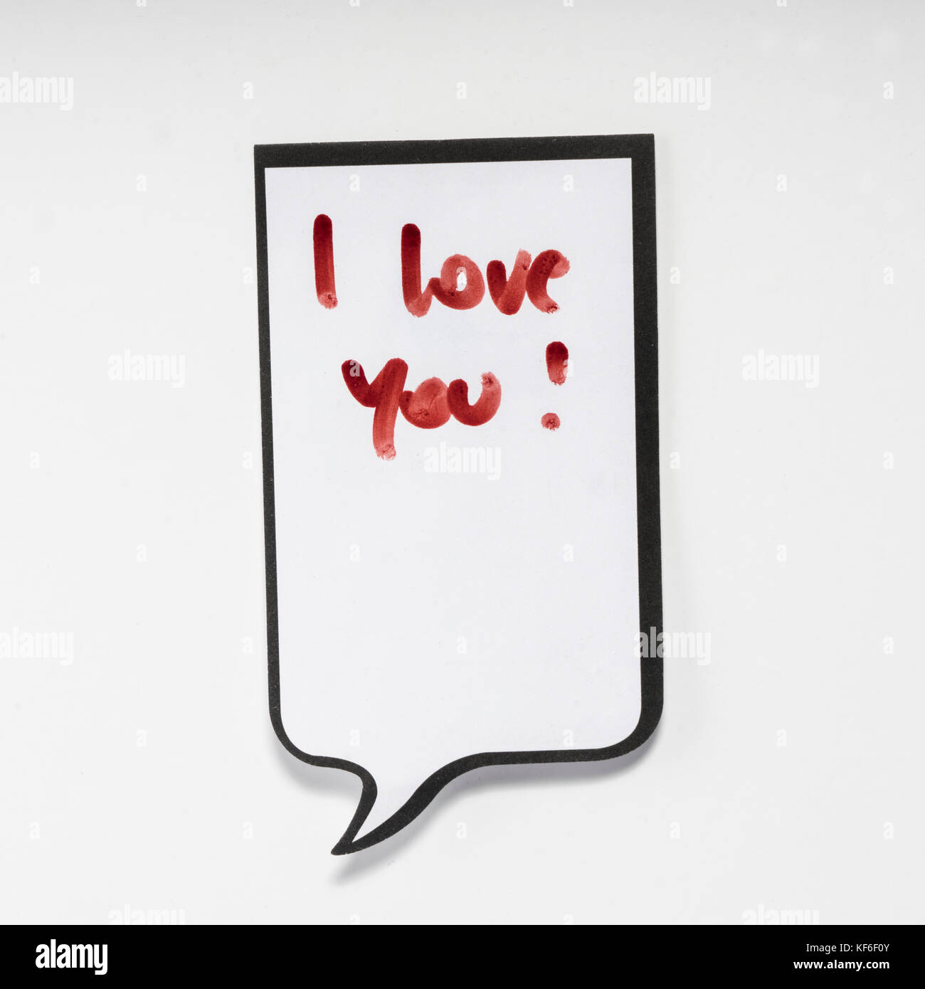 a white memo pad with the shape of a comic with the inscription 'I love you' - Stock Image