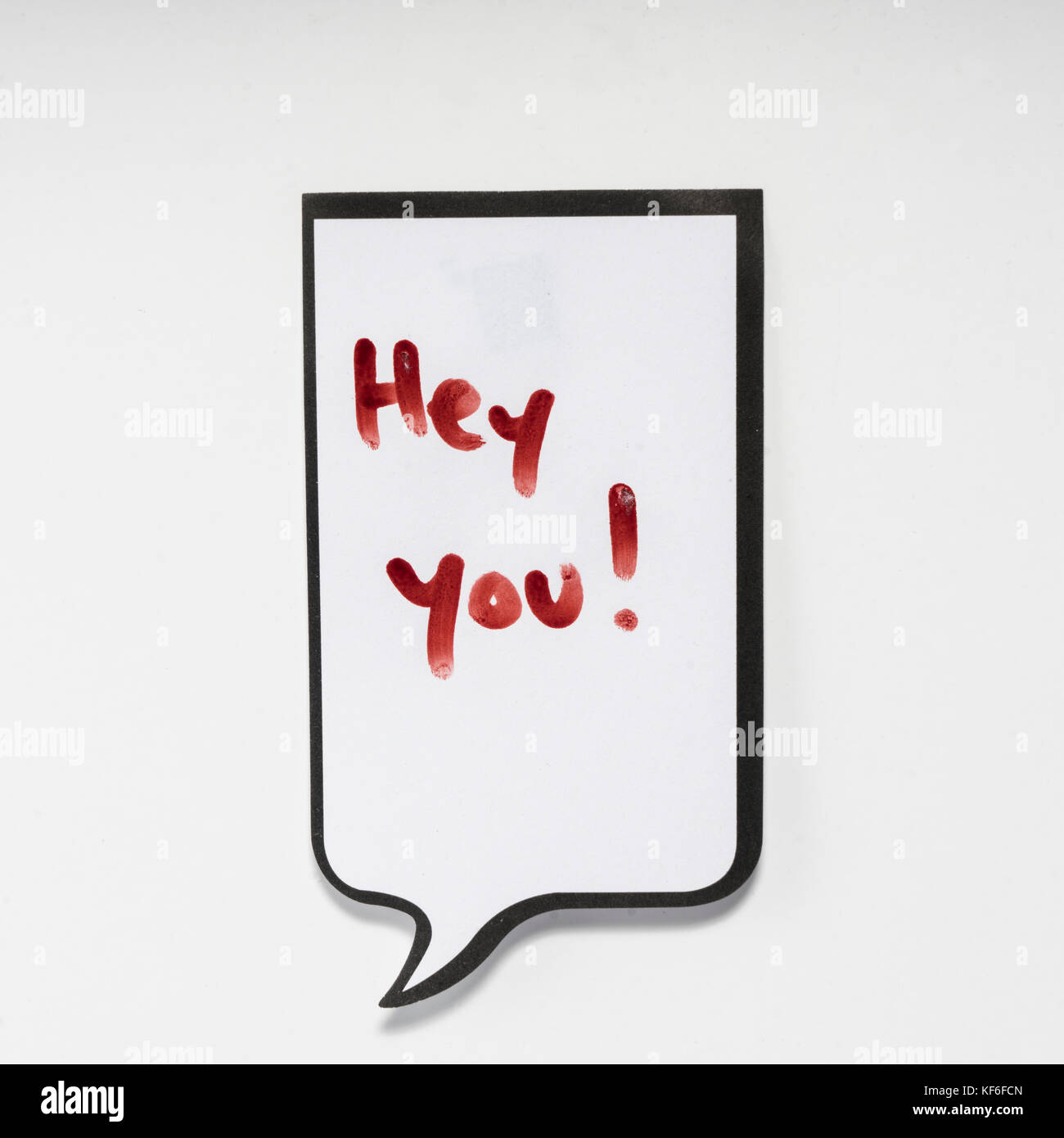 a white memo pad with the shape of a comic with the inscription 'hey you' - Stock Image